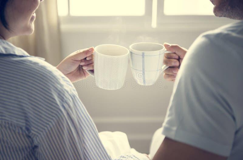 Pares felices que celebran con las tazas de café foto de archivo