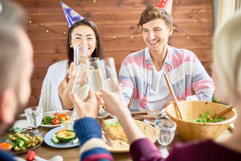 Pares felices que celebran cumpleaños en la cena imagen de archivo