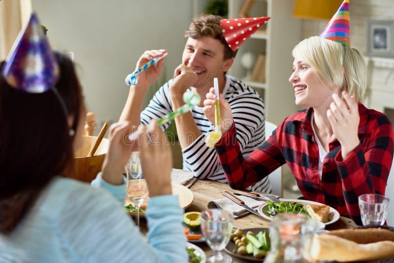 Pares felices que celebran cumpleaños en la tabla de cena fotos de archivo