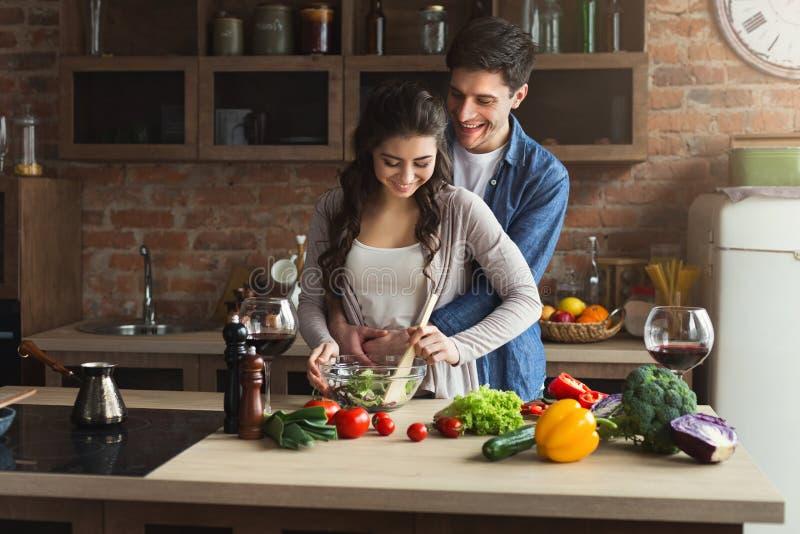 Pares felices que cocinan la comida sana junta fotos de archivo