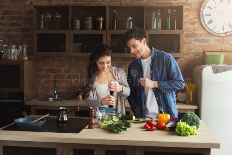 Pares felices que cocinan la comida sana junta foto de archivo libre de regalías