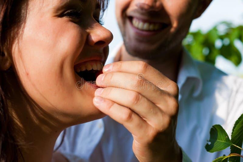 Pares felices que comen cerezas en verano fotos de archivo libres de regalías