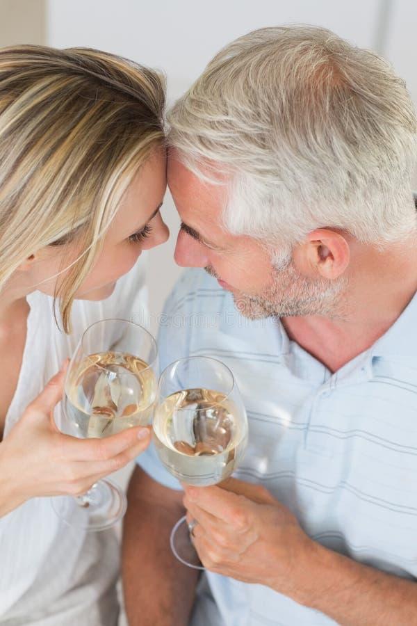 Pares felices que comen el vidrio de vino junto fotografía de archivo libre de regalías