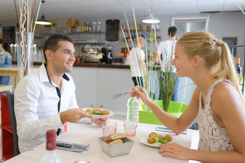 Pares felices que comen en el restaurante fotografía de archivo