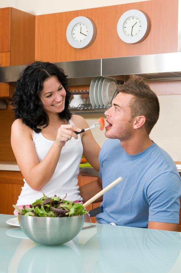 Pares felices que comen juguetónamente la ensalada en la cocina fotografía de archivo