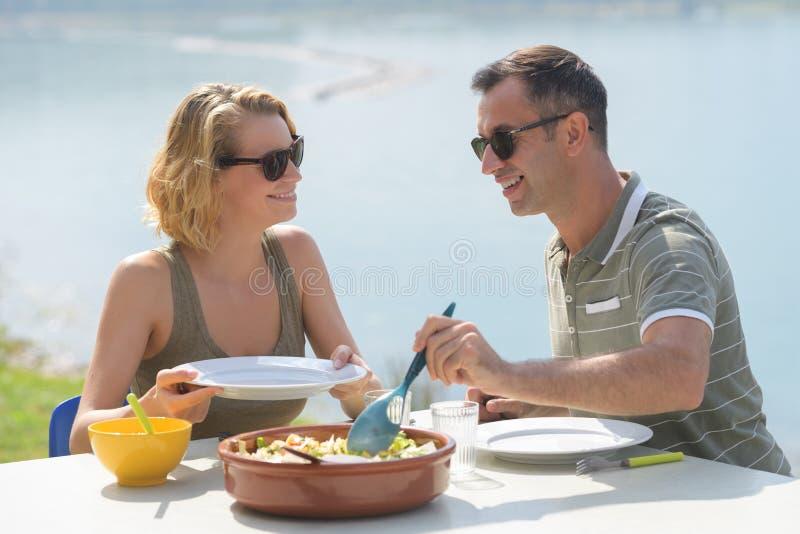 Pares felices que comen la ensalada para la cena en la terraza del restaurante foto de archivo libre de regalías