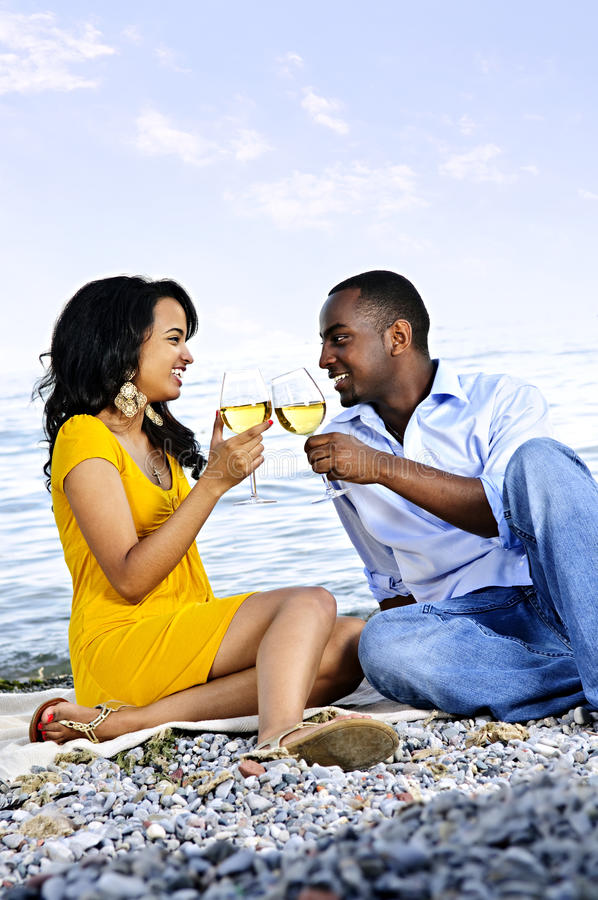 Pares felices que comen vino en la playa imágenes de archivo libres de regalías