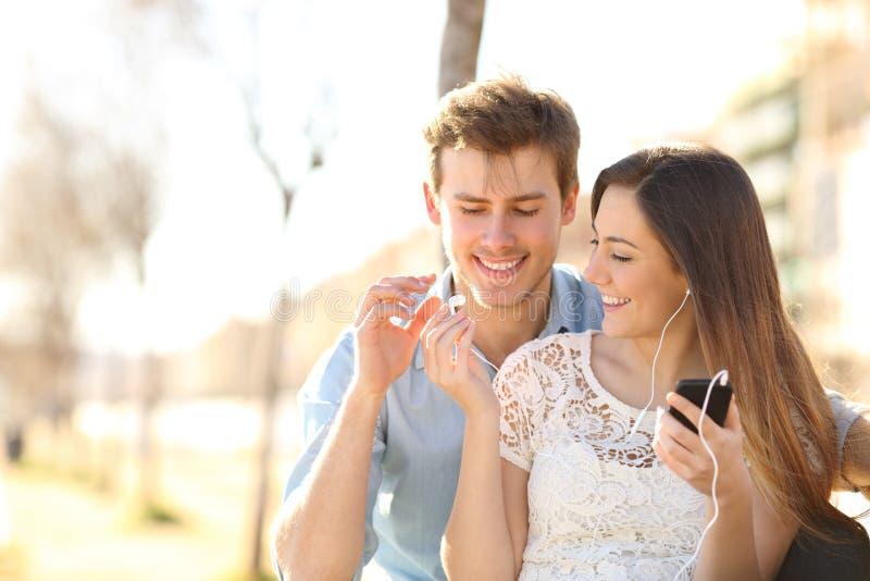 Pares felices que comparten auriculares de botón para escuchar la música fotos de archivo