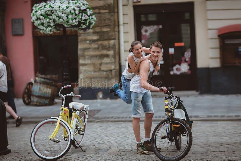 Pares felices que completan un ciclo en la ciudad imagen de archivo libre de regalías