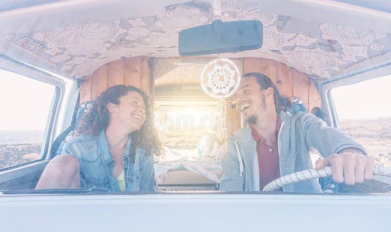 Pares felices que conducen un minivan y que ríen mientras que mira uno a - gente joven que se divierte durante un roadtrip el ver fotos de archivo libres de regalías