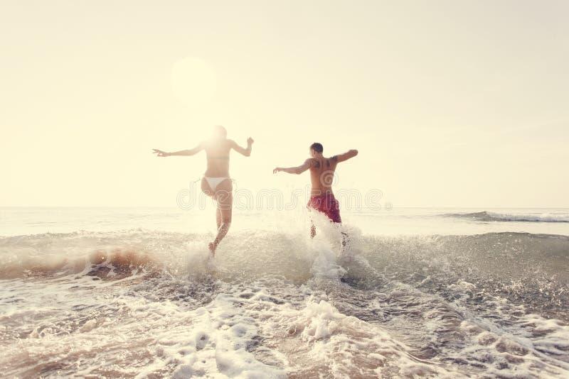 Pares felices que corren al mar fotos de archivo