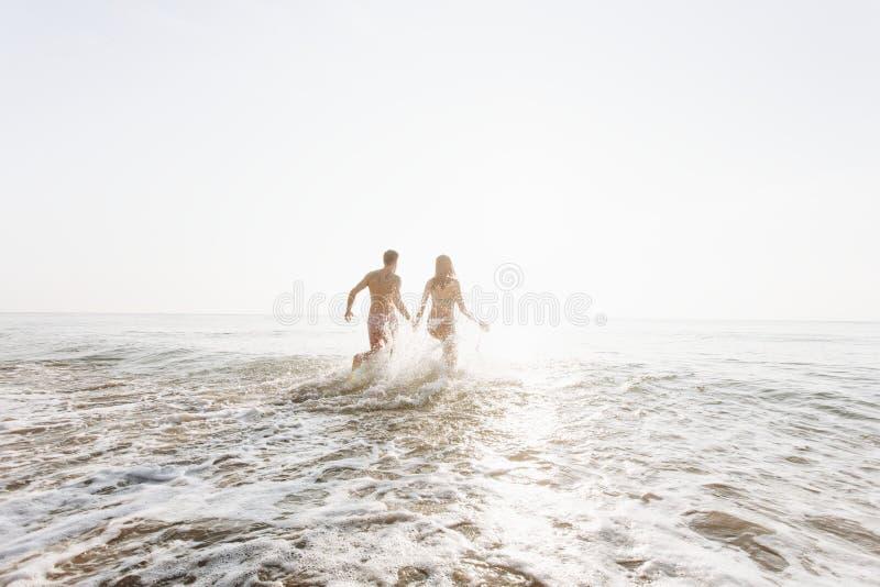 Pares felices que corren en el agua imagenes de archivo