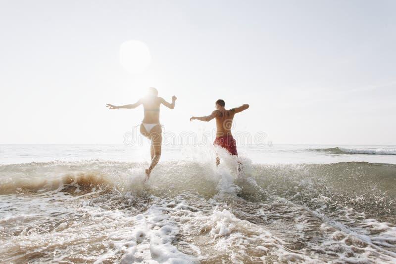 Pares felices que corren en el agua imagen de archivo libre de regalías