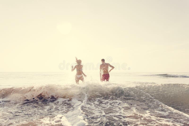 Pares felices que corren en el agua fotografía de archivo