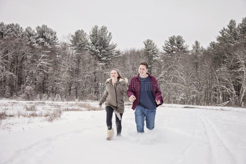 Pares felices que corren en nieve imagen de archivo libre de regalías
