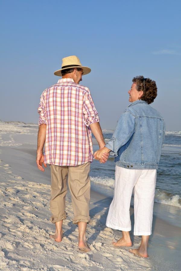 Pares felices que dan un paseo en la playa en la puesta del sol fotografía de archivo libre de regalías