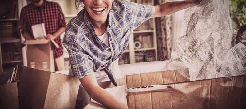 Pares felices que desempaquetan los cartones juntos fotos de archivo libres de regalías
