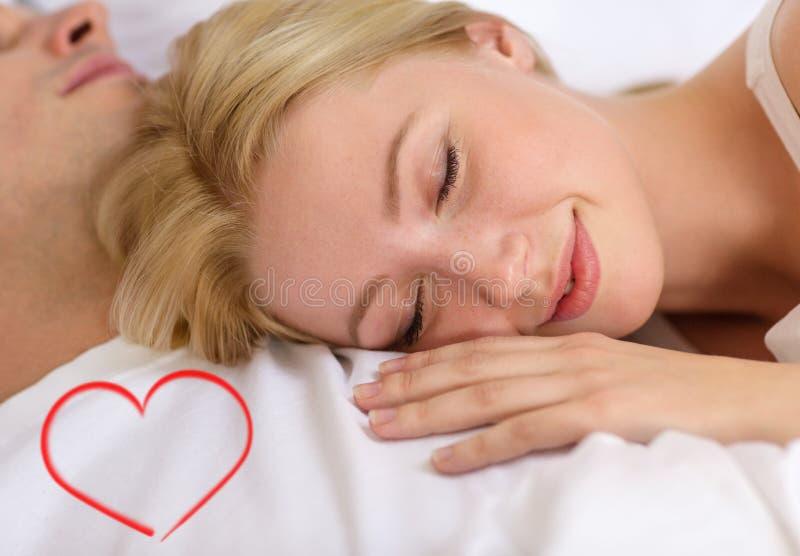 Pares felices que duermen en cama fotografía de archivo libre de regalías
