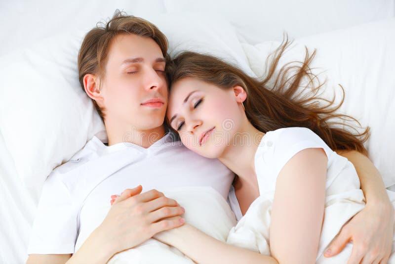 Pares felices que duermen en cama en casa imágenes de archivo libres de regalías