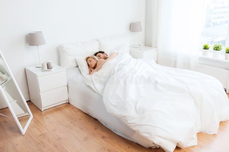 Pares felices que duermen en cama en casa foto de archivo libre de regalías