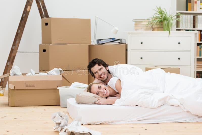 Pares felices que duermen en el piso en un nuevo hogar imagen de archivo libre de regalías