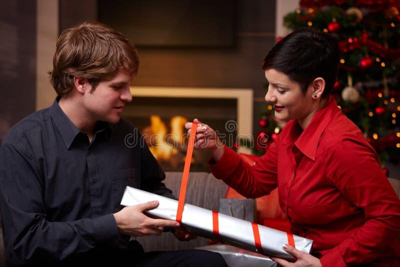 Pares felices que envuelven regalos de Navidad imagen de archivo