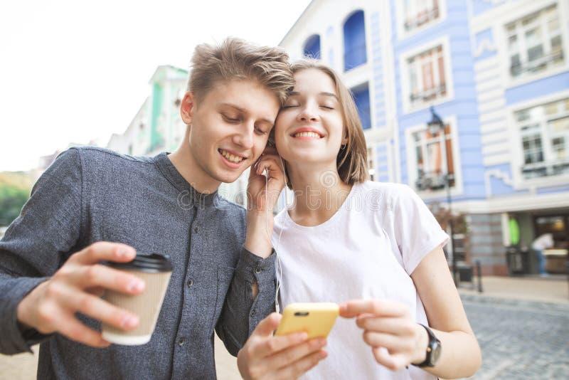 Pares felices que escuchan la música en un auricular dos Hombre joven feliz con un vidrio de café en sus manos fotos de archivo
