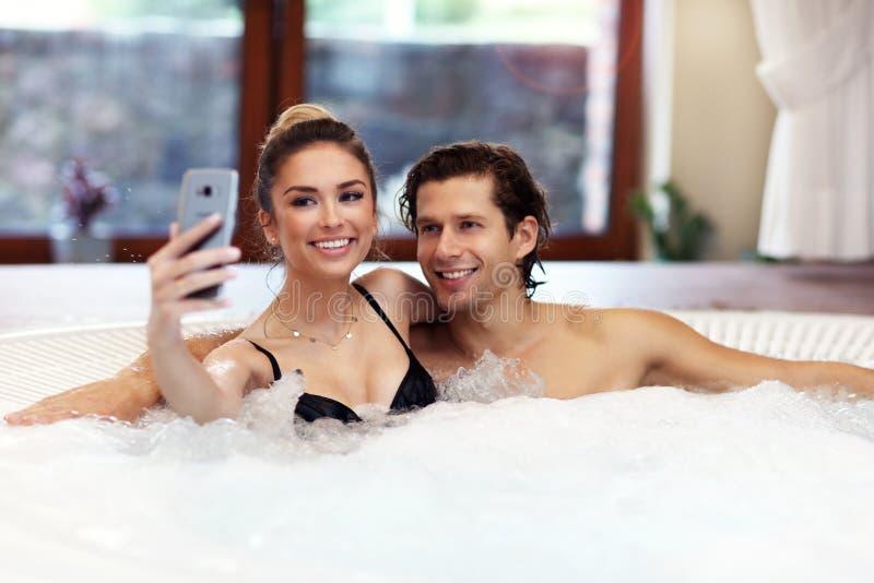 Pares felices que gozan del Jacuzzi en balneario del hotel foto de archivo
