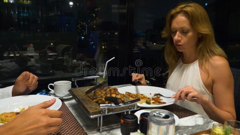 Pares felices que hablan y que cenan en rascacielos de desatención de una barra, por la tarde, imagenes de archivo