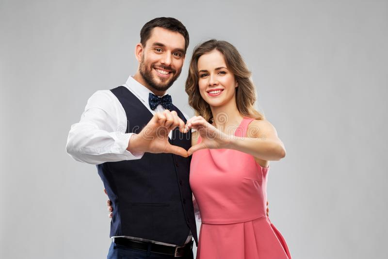Pares felices que hacen el corazón de la mano en día de San Valentín fotos de archivo