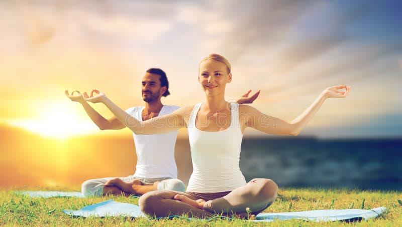 Pares felices que hacen yoga y que meditan al aire libre foto de archivo libre de regalías