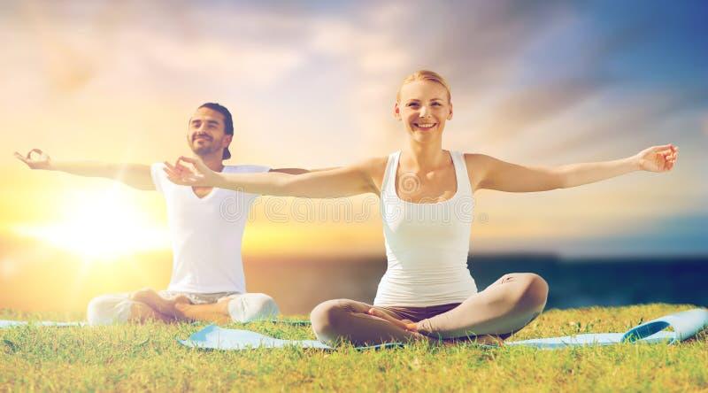 Pares felices que hacen yoga y que meditan al aire libre imagen de archivo libre de regalías