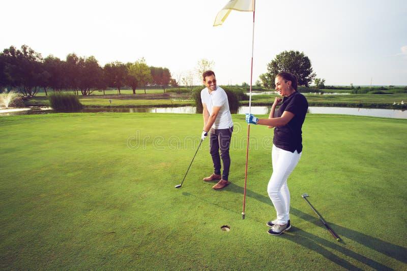 Pares felices que juegan a golf en el club foto de archivo libre de regalías