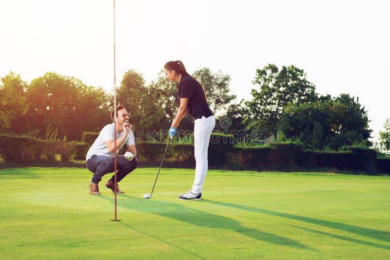 Pares felices que juegan a golf en el club imagen de archivo libre de regalías