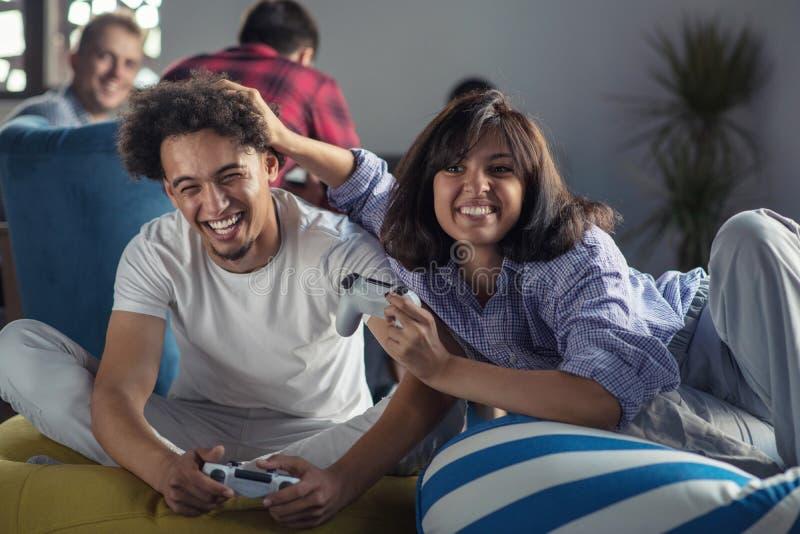 Pares felices que juegan a los videojuegos en la oficina de lanzamiento moderna fotografía de archivo