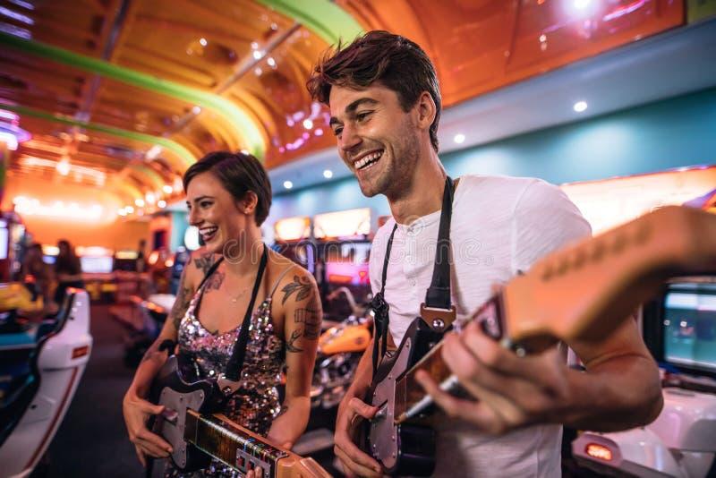 Pares felices que juegan a un juego de arcada de la guitarra fotos de archivo libres de regalías