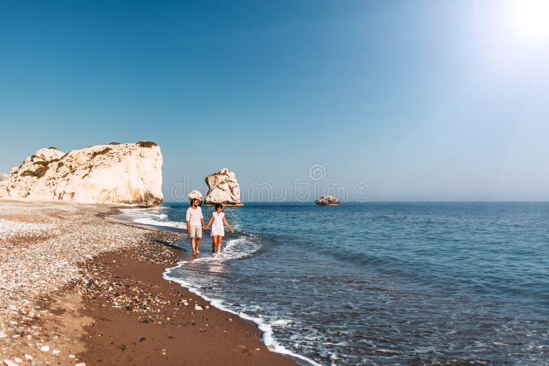 Pares felices que llevan a cabo las manos que caminan en la playa arenosa Pares en amor en la puesta del sol por el mar Pares en  fotos de archivo libres de regalías