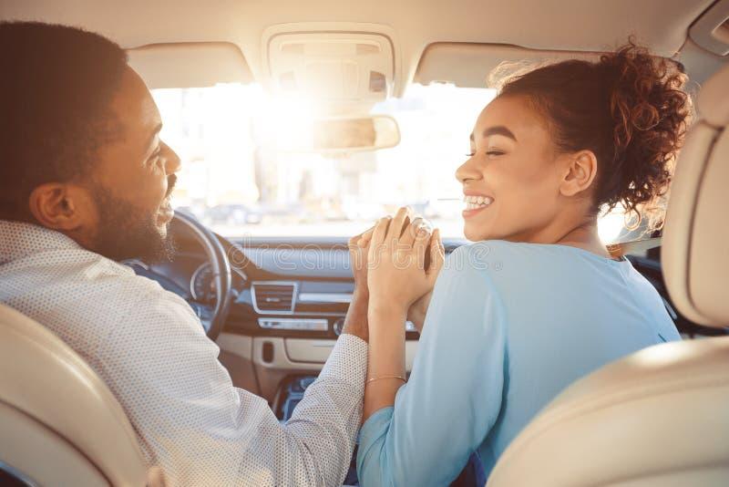 Pares felices que llevan a cabo las manos, viajando en coche foto de archivo libre de regalías
