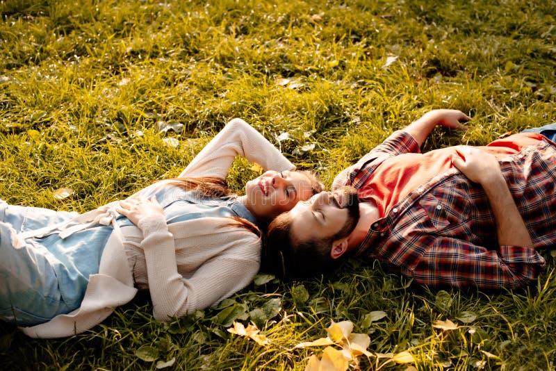 Pares felices que mienten en hierba en el parque del otoño, cabeza fotografía de archivo