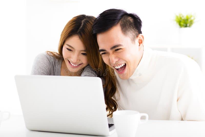 Pares felices que miran el ordenador portátil en sala de estar imagen de archivo libre de regalías