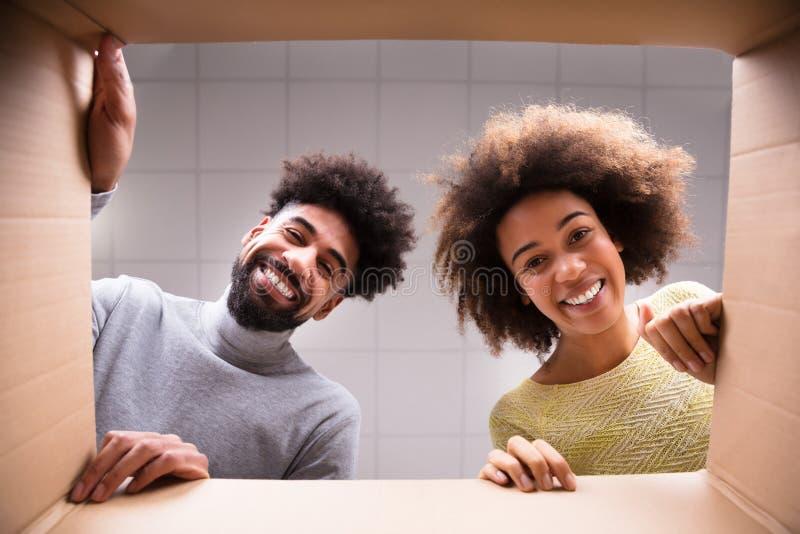 Pares felices que miran la caja de cartón interior imagen de archivo libre de regalías