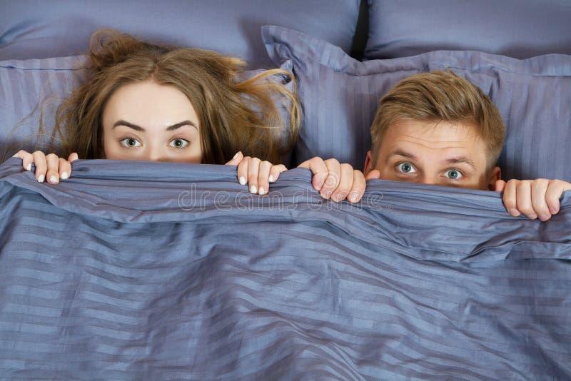 Pares felices que ocultan debajo de la manta en cama Pares en dormitorio por la ma?ana imagen de archivo