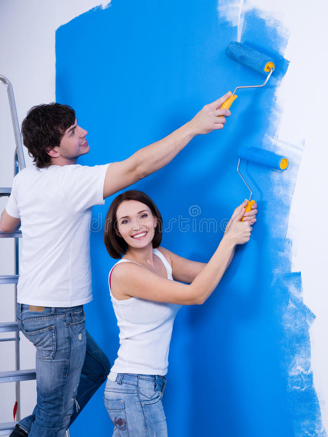 Pares felices que pintan la pared