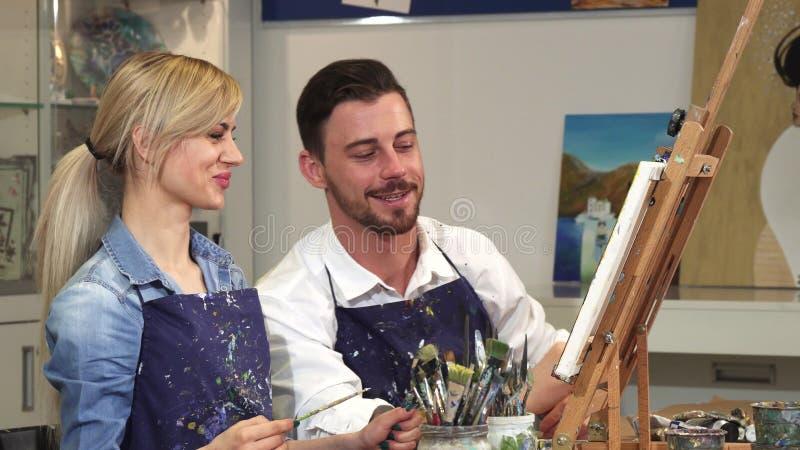 Pares felices que pintan una imagen junto una fecha en Art Studio fotografía de archivo libre de regalías