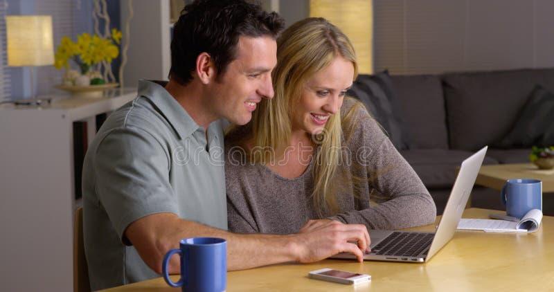 Pares felices que practican surf Internet junto foto de archivo