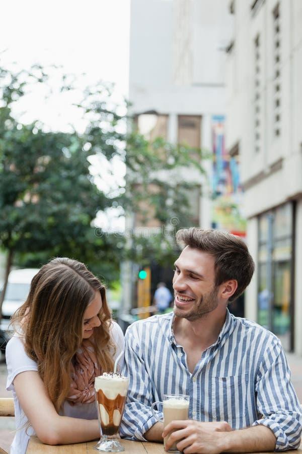 Pares felices que ríen mientras que bebe el café frío en el café de la acera fotografía de archivo libre de regalías