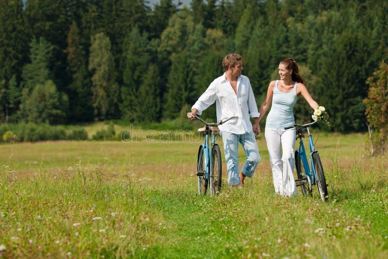 Pares felices que recorren con las bicis pasadas de moda fotografía de archivo libre de regalías