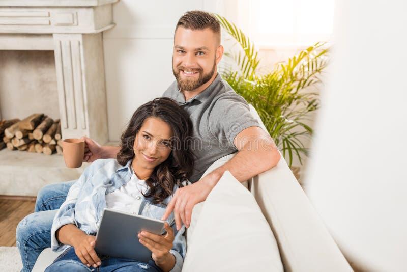 Pares felices que relajan y que usan la tableta digital mientras que se sienta en el sofá en casa foto de archivo libre de regalías