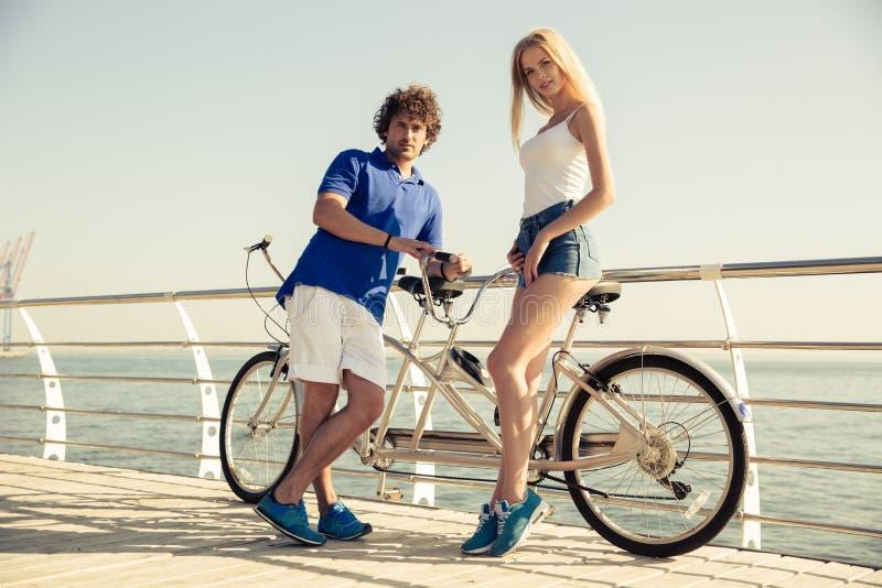 Pares felices que se colocan cerca de la bicicleta en tándem imagenes de archivo