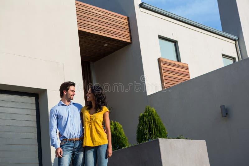 Pares felices que se colocan delante de nueva casa imagen de archivo